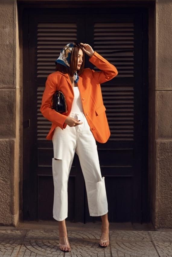 Siêu mẫu chuyển sang phong cách thanh lịch với áo blazer màu cam rực rỡ, kết hợp áo thun ôm sát và quần ống rộng.