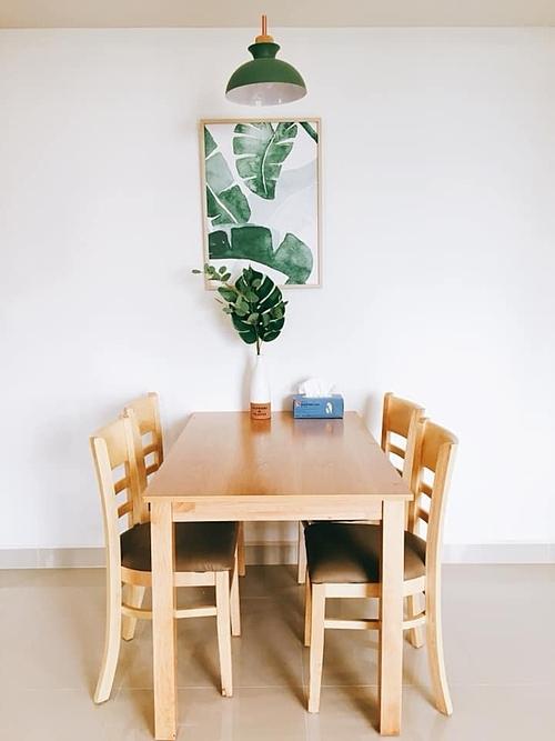 Nhung Phùng chọn bộ bàn ăn có thiết kế cơ bản và treo thêm tranh hình lá, bày lọ hoa, treo đèn để tạo điểm nhấn. Cô lựa chọn toàn bộ đèn màu vàng cho căn hộ để tạo cảm giác ấm cúng, sang và không bị lóa mắt.
