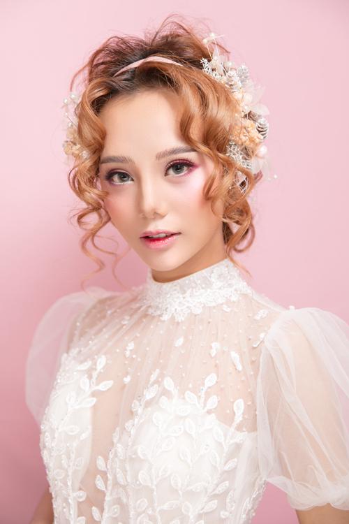 Cô dâu như biến hóa thành nàng búp bê nhờ phấn má hồng. Chuyên gia sử dụng má hồng dạng lì để lớp trang điểm bám màu lâu hơn.