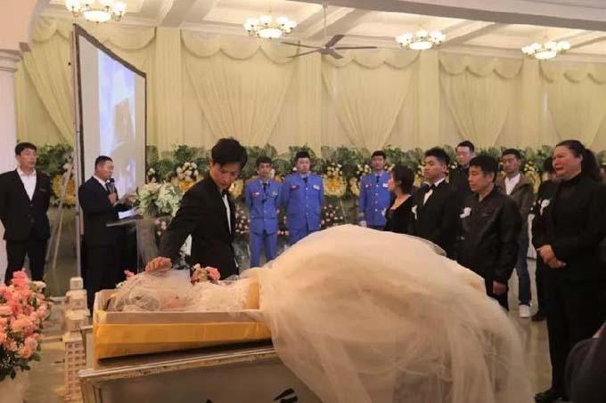Xu buồn bã đứng bên chiếc quan tài có thi hài vợ mặc váy cưới nằm trong. Ảnh: CQCB.