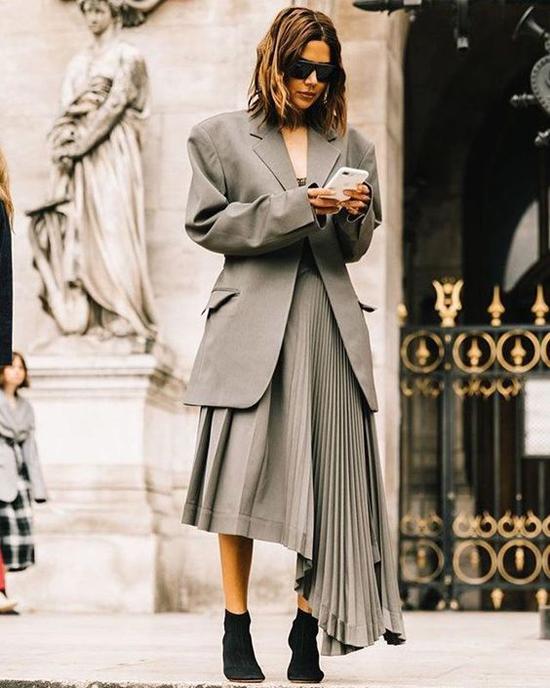 Set đồ cho nàng cá tính với balzer dáng rộng, chân váy bất đối xứng được xử lý đường xếp ly bắt mắt.