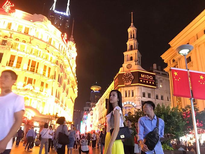 Cách không xa bến Thượng Hải là phố Nam Kinh - đại lộ Champs Elysees của Trung Quốc với vô vàn cửa hàngtừ bình dân đến cao cấp. Con đườngnày hiện được quy hoạch là phốđi bộ dành cho du khách tham quan, mua sắm. Để tái hiện lại nhịp sống của thành phố những năm 1930, người ta còn vận hành một tuyến tàu điện dành riêng cho du lịch, chạy dọc theo con phố và reo chuông leng keng. Thúy An không quên check in ở tháp đồng hồ đặc trưng nhất trên con phố này.