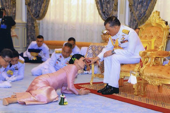 Suthida nửa nằm nửa quỳ dưới chân Quốc vương Maha Vajiralongkorn trong lễ cưới theo phong tục hoàng gia hôm 1/5. Ảnh: AFP.