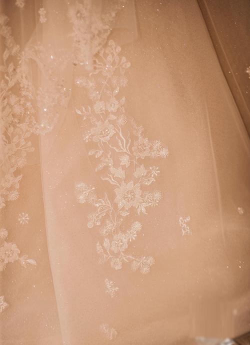 ... và chất liệu vải dệt sequin đính hoa dây leo. Từng nhánh hoa nhỏ nhắn được những người thợ thủ công cắt tỉa tỉ mỉ và đính trải dài trên thân váy, tôn nét mềm mại cho vóc dáng nàng dâu.