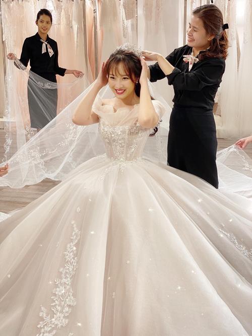 Cô dâu kết hợp cùng một chiếc khăn voan dài (train veil) đính hoa ren đồng điệu với thân váy.
