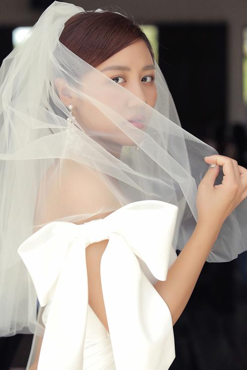 NTK Võ Thanh Can khai thác chất liệu chủ đạo phi lụa mờ cho bộ cánh, voan lưới làm lúp, sử dụng điểm nhấn vừa phải nơi cầu vai.Người đẹp diện váy với layout makeup đơn giản, tóc ngắn chải lệch và dùng thêm phụ kiện hoa tai dáng dài.