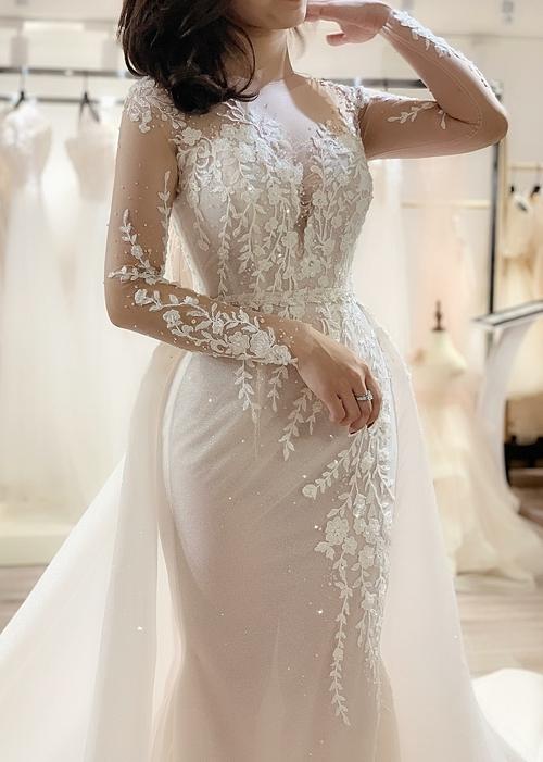 Độ bắt sáng của váy có chiều sâu nhờ những lớp vải dệt sequinvà vô số hạt pha lêđính xen kẽ trên các cánh hoa.