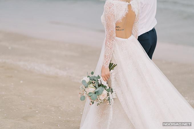 Mặt lưng váy được cắt xẻ tạo eo thon, đính kết pha lê cao cấp dọc thân giúp tôn diện mạo tân nương.