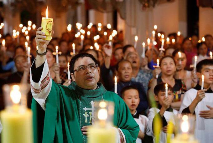 Linh mục Anthony Dang Huu Nam (nguyên quán Nghệ An) cầm nến tổ chức lễ tưởng niệm, cầu nguyện cho 39 nạn nhân trong container. Ảnh: Reuters.