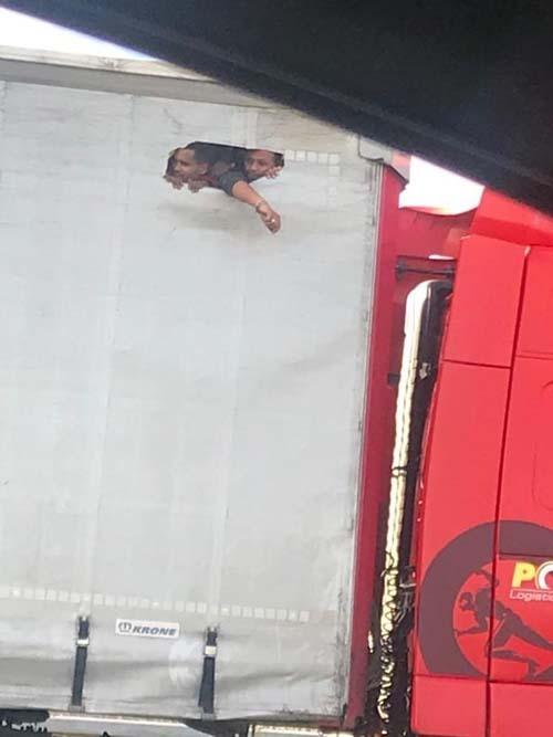 Những người nhập cư nhìn ra ngoài đường cao tốc qua cái lỗ trên thùng xe tải hôm 17/10. Ảnh: publicityagent.co.uk.
