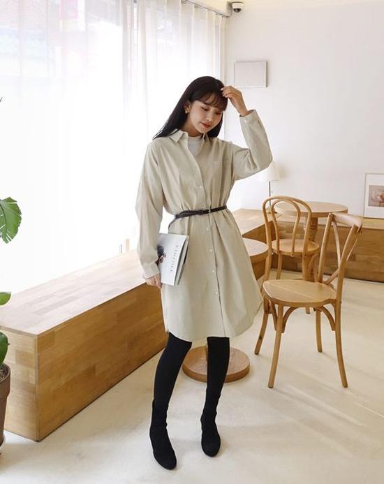 Phong cách trẻ trung cho nàng công sơ với đầm sơ mi vải thô kết hợp cùng áo thun basic, bốt cổ cao và quần tất tông đen.