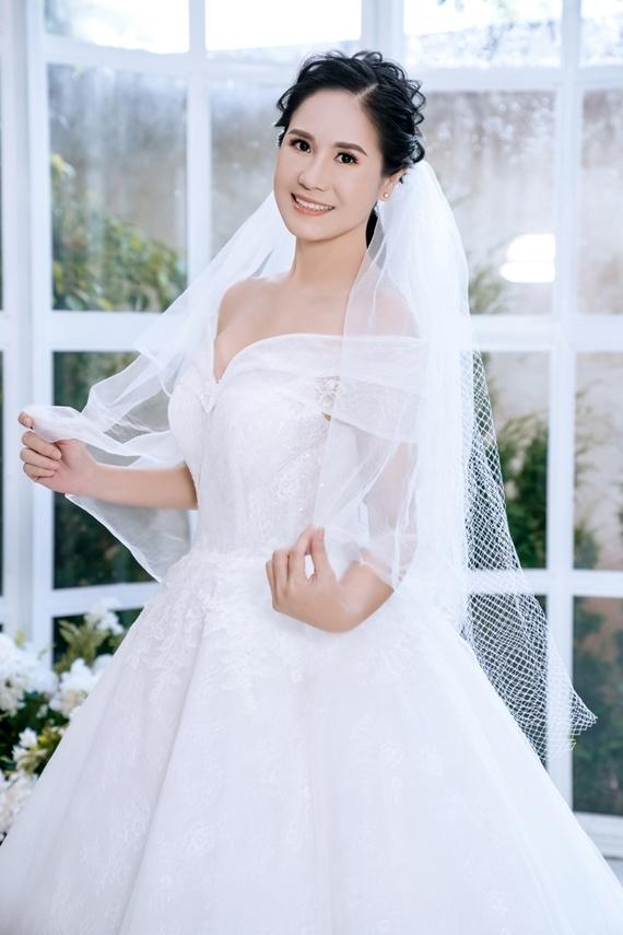 Diễn viên Đào Vân Anh diện váy cưới trễ vai màu trắng, khoe nhan sắc rạng rỡ dù đã bước sang tuổi 50.