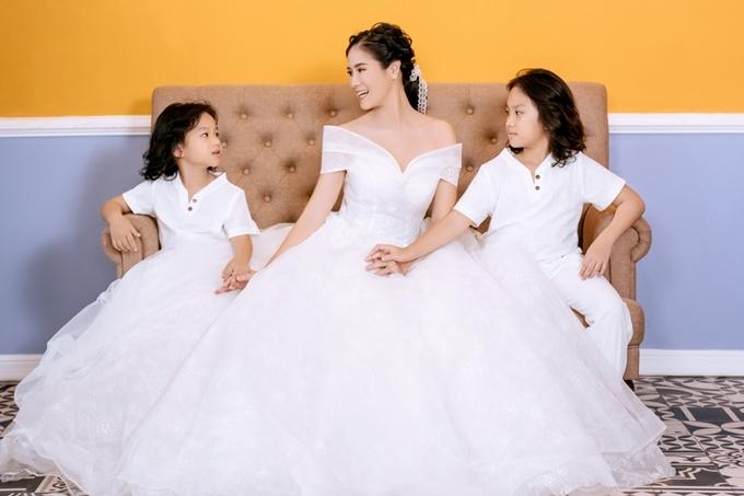 Hai nhóc tỳ rất hiếu động, đùa nghịch với váy cưới của mẹ, tạo nên những khoảnh khắc vui tươi, ý nghĩa cho ba mẹ con.