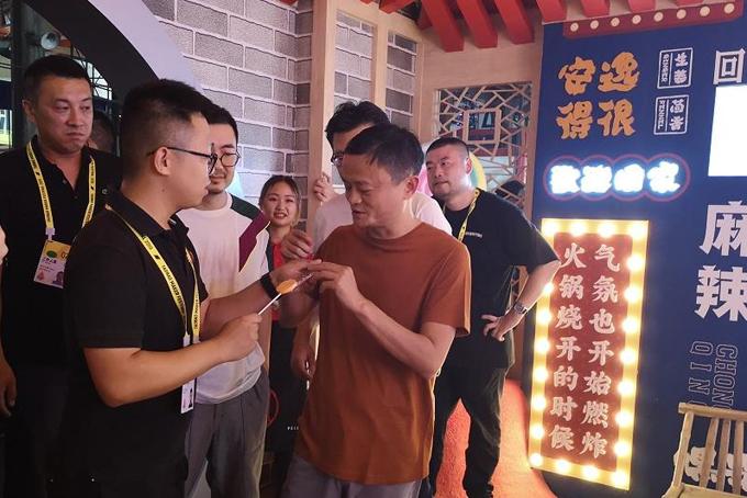 Jack Ma thử món kẹo mút cay tại gian hàng của nhà hàng lẩu Peijie. Ảnh: Chinadaily.