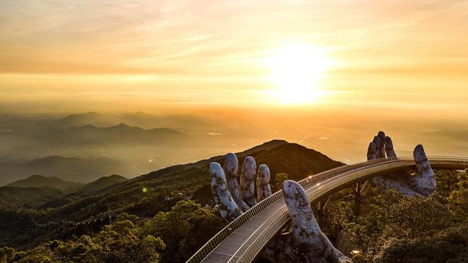 Và điểm đến thu hút du khách từ khắp nơi trên thế giới đổ về là Cầu Vàng. Với thiết kế đôi bàn tay của thần núi nâng dải lụa vàng, cây cầu đã đưa cái tên Bà Nà vượt ra khỏi biên giới, trở thành một hiện tượng, cơn sốt suốt thời gian qua.