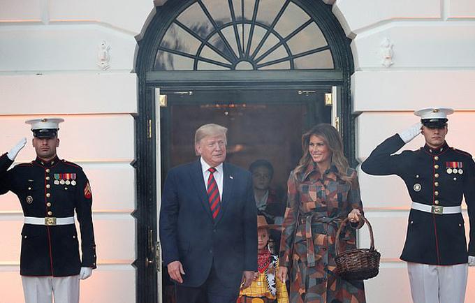 Sẩm tối 28/10, ông Trump và vợ xuất hiện trước cửa ra vào của Nhà Trắng nhân dịp Halloween truyền thống. Tuy nhiên, cặp vợ chồng quyền lực của nước Mỹ không chọn đồ hóa trang mà vẫn mặc trang phục như bình thường. Trong khi Tổng thống Mỹ diện vest, vợ của ông - bà Melania - chọn một chiếc váy dài quá đầu gối với họa tiết vàng đỏ phù hợp với tiết thu.