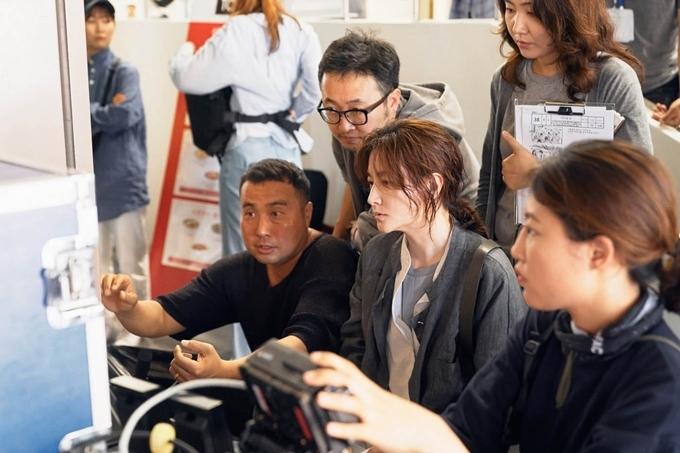 Lee Young Ae xem lại cảnh phim và trao đổi với đạo diễn trên trường quay.