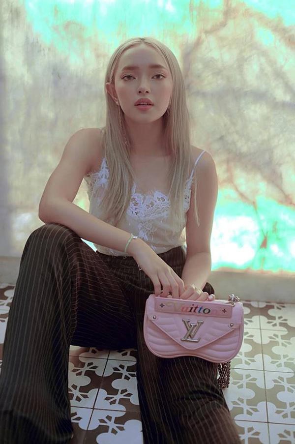 Áo hai dây trắng kết hợp với quần âu dáng suông và túi xách Louis Vuitton màu hồng nhạt giúp người đẹp trở nên ngọt ngào, nữ tính.