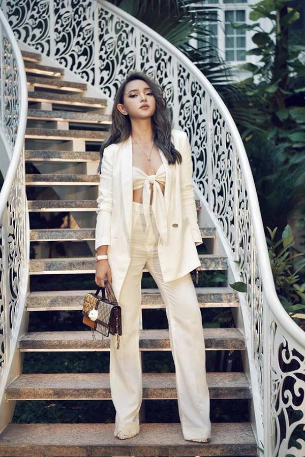Bộ suit màu trắng trở nên gợi cảm hơn khi được phối với áo bra thắt nơ cùng chất liệu. Châu Bùi mặc quần dài trùm giày cao gót để ăn gian chiều cao và tiết chế phụ kiện để set đồkhông trở nên rối mắt nếu có quá nhiều điểm nhấn.