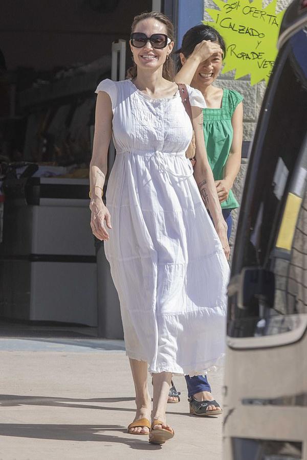 Bà mẹ 6 con mặc váy đơn giản, xỏ dép lê đi mua sắm.