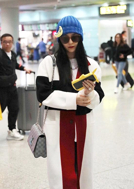Nữ diễn viên đội mũ len gắn logo chối nổi bật, cắp theo pikachu, điện thoại vàng rực.  Trên tay cô là chiếc nhẫn kim cương lấp lánh.