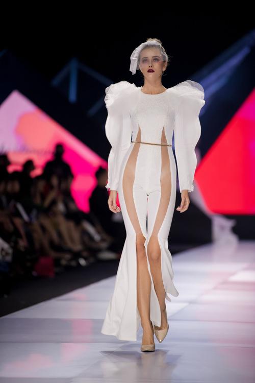 Jumpsuit có các dải xuyên thấu dọc thân. Cánh tay từ vải tulle xếp nếp tạo điểm hút ánh nhìn. NTK giúp thu gọn vòng eo của cô dâu nhờ sử dụng phụ kiện thắt lưng màu vàng đồng.