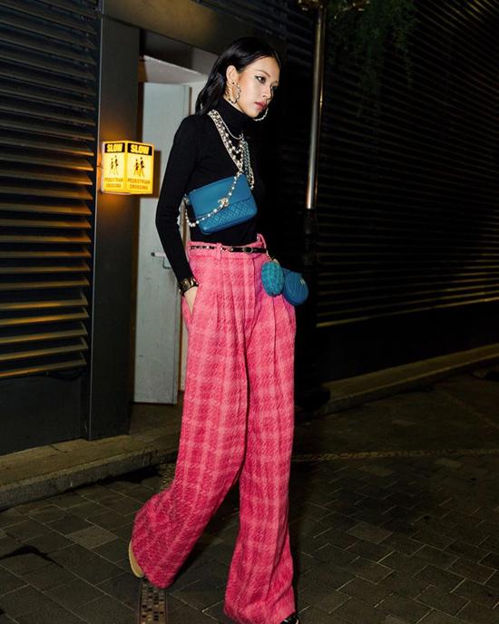 Áo cổ lọ tông đen được Phí Phương Anh phối hợp với những tông màu bắt mắt như xanh dương của bộ phụ kiện Chanel và quần hồng ống rộng.