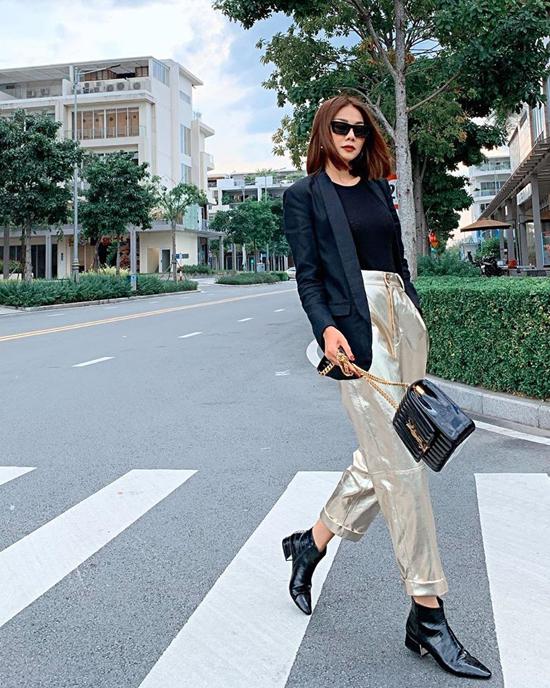 Quần ánh kim là trang phục Thanh Hằng chọn lựa để tô điểm cho set đồ toàn tông đen gồm áo blazer, áo thun, túiYves Saint Laurent và bốt cổ thấp.