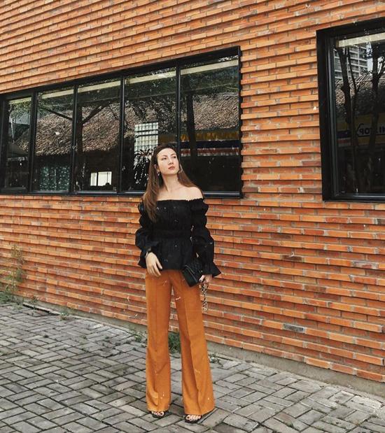 Yến Nhi chọn áo trễ vai để mix cùng quần suông ống rộng màu nâu trầm ấm - một trong những tông màu luôn được ưa chuộng ở xu hướng thu đông.