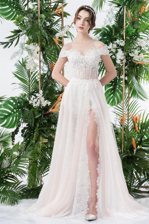 Các mảng hoa ren từ chỉ tơ trên nền váy trắng giúp cô dâu khoe nét đẹp hình thể. Thiết kế xẻ đùi thể hiện vẻ gợi cảm nơi đôi chân thon.