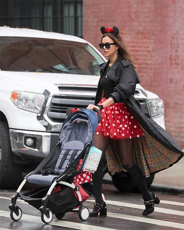 Dù mặc trang phục trẻ con, Irina vẫn phối đồ sành điệu với áo choàng Burberry. Siêu mẫu Nga sải bước trên phố như đi sàn catwalk.