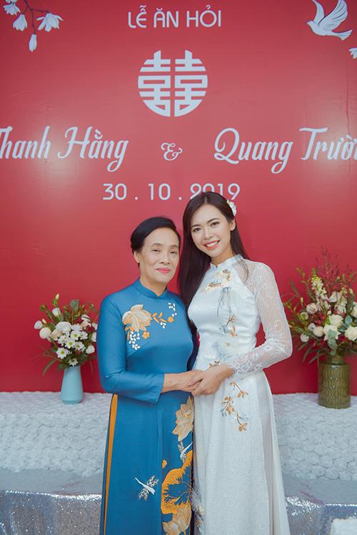 Thanh Hằng bên mẹ ruột. Cô dâu diện áo dài cưới mang phom dáng truyền thống với tay áo ren xuyên thấu, cổ trụ thấp. Người đẹp chọn tông makeup màu cam tươi tắn, trẻ trung.