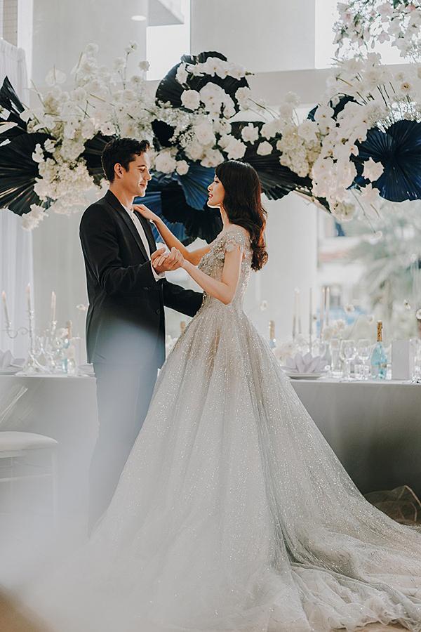 Hạ Vi hóa cô dâu xinh đẹp trong bộ váy màu bạc ánh kim lộng lẫy, khoe bờ vai trần gợi cảm. Còn Kevin là chủ rể điển trai, thanh lịch với bộ vest đen cùng áo sơ mi trắng cổ tàu.