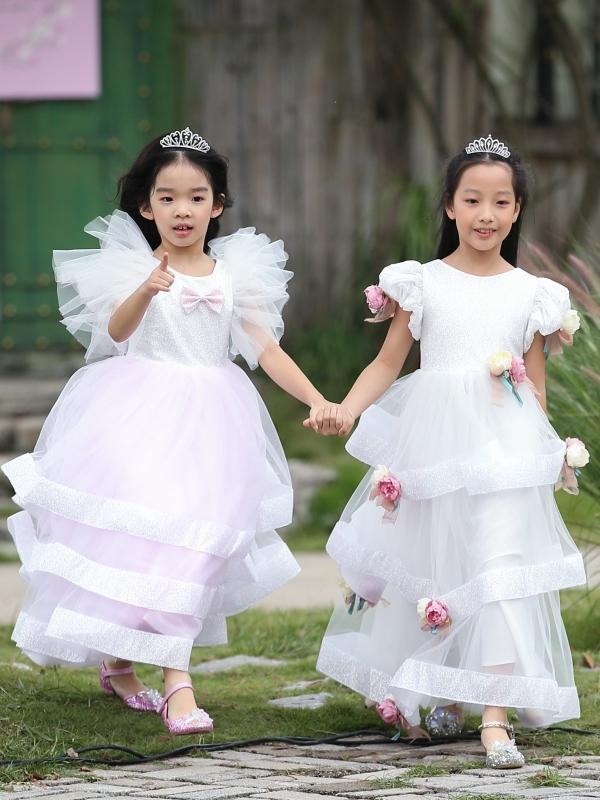 Bé Thỏ (trái) dạn dĩ catwalk nhờ có nhiều kinh nghiệm trình diễn trước đó. Cô bé nắm tay người bạn Anh Thư đảm nhận vedette bộ sưu tập Little Stars.