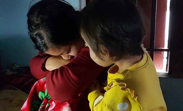 Chị Thái Thị Giang (áo đỏ) bên con gái nhỏ liên tục nấc nghẹn khi nhắc tên chồng. Ảnh: Hải Bình.