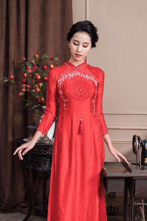 Áo dài đỏ của nữ cũng làm từ vải in chìm, có thêm họa tiết thêu nhành hoa nhẹ nhàng, điểm hạt ngọc đối xứng nơi dọc tà, viền tay áo, viền cổ áo tạo sự bắt sáng tự nhiên.