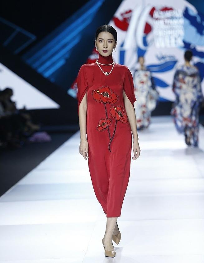 Áo dài được cách điệu độc đáo với phom dáng ngắn cùng những bông hoa thêu tỉ mỉ, đính đá lấp lánh cùng tông đỏ thanh lịch.
