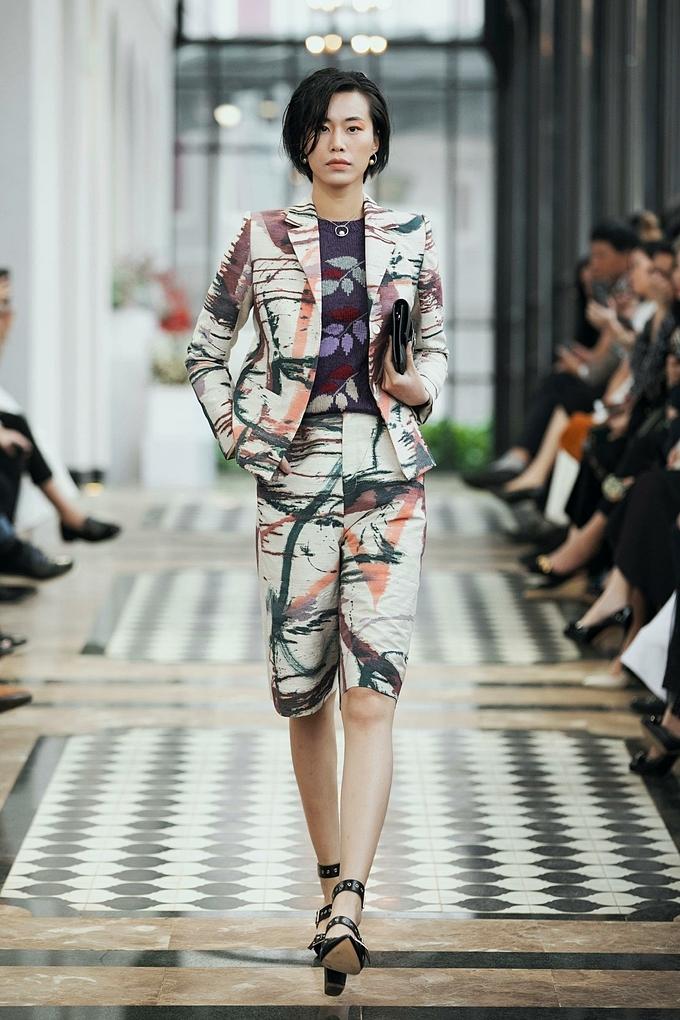 Một trong những phối chọn của NTK Lê Thanh Hòa khi bộ suit hoa văn Tây Bắc trở nên đồng bộ với chiếc túi bán nguyệt và đôi giày cao gót đính kim loại.