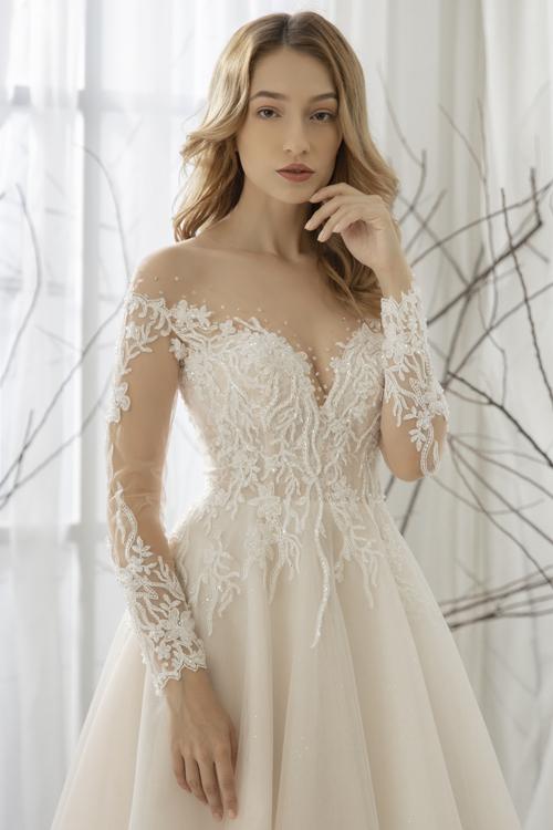 Nhóm thiết kế sử dụng chất liệu voan mỏng cho cổ và tay áo, điểm thêm ren, pha lê, mang đến nét đẹp quyến rũ cho cô dâu khi diện váy.