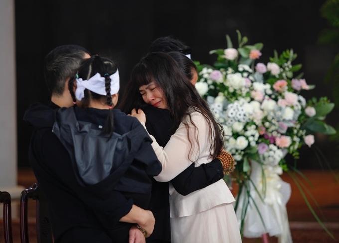 Bạn bè ôm ghì chị Hồng Phượng để chia sẻ mất mát. Anh Thành bồng con gái út lên tay.