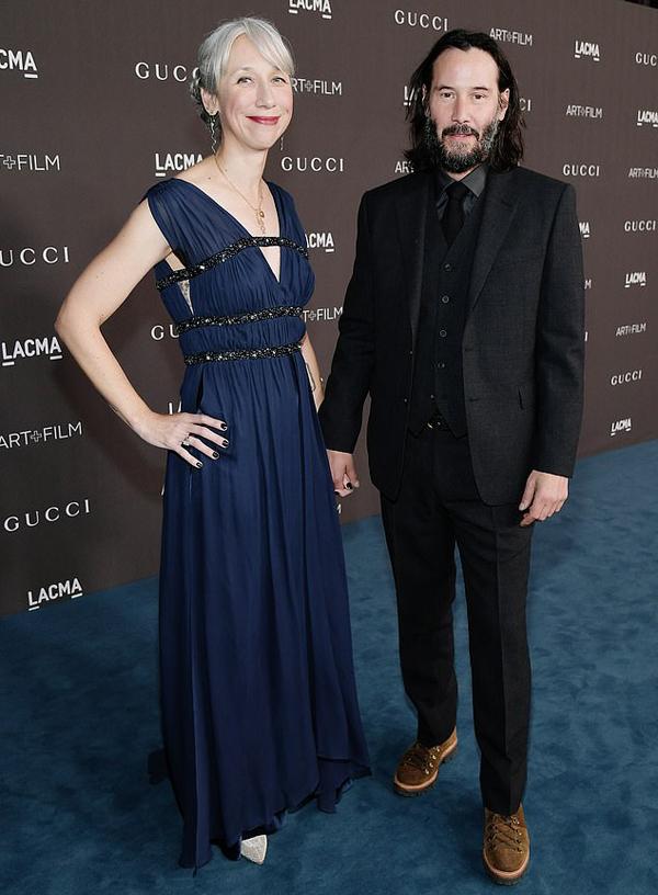 Keanu Reeves tay trong tay họa sĩ Alexandra Grant tại sự kiện tối chủ nhật. Ảnh: AFP.