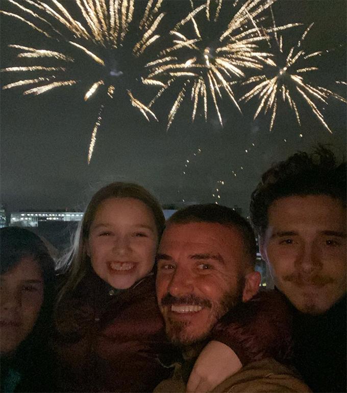 Cô út Harper khoác vai bố Becks khi chụp ảnh selfiecùng pháo hoa. Ảnh: Instagram.
