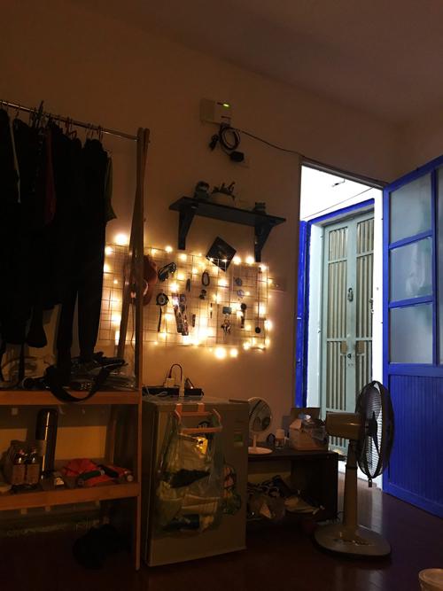 Dũng sử dụng đèn trang trí và sơn cánh cửa màu electric blue (xanh điện) tạo điểm nhấn làm sáng bừng căn hộ.