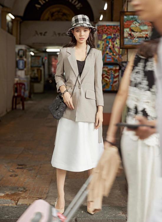 Jolie Nguyễn theo phong cách tối giản khi chọn áo blazer xám ghi để mix cùng áo thun đen và chân váy midi trắng.