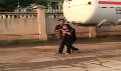 Đào Xuân Hưng kề dao vào cổ chị Hà, gây sức ép để chạy trốn. Ảnh cắt từ clip.