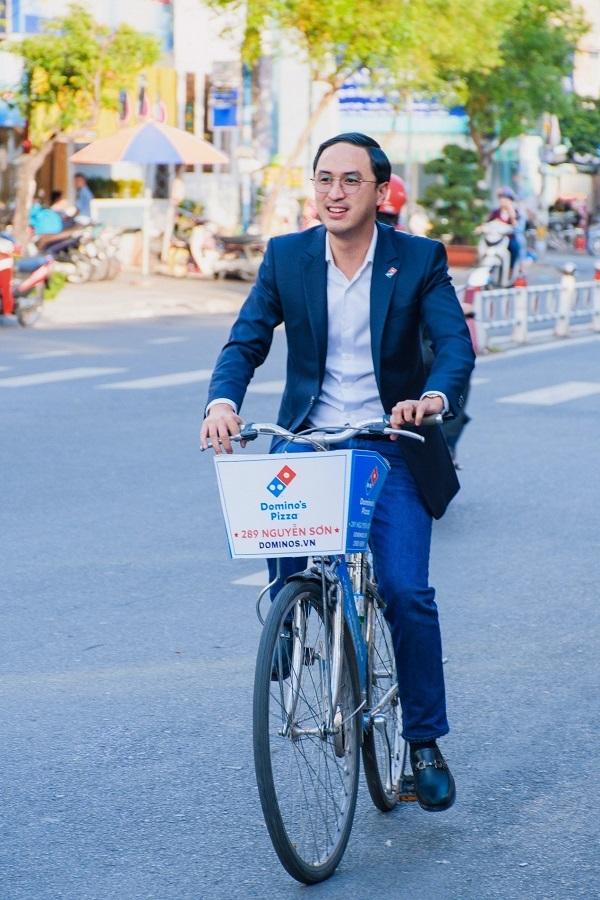 Doanh nhân Louis Nguyễn -CEO Dominos Việt Nam -diện vest lịch lãm, chạy xe đạp khởi động cho chuỗi chương trình khai trương cửa hàng Dominos Pizza thứ 40 tại quận Tân Phú.