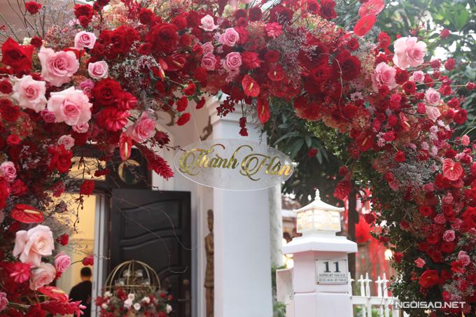 Tư gia nhà trai được trang trí với các loại hoa gồm hoa hồng, hồng môn, các loại lá bụi phụ trợ. Bảng chữ của lễ thành hôn mang sắc vàng đồng hiện đại.
