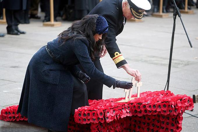 Vợ chồng Meghan - Harry cắm thánh giá tưởng niệm ở Tu viện Westminster sáng 7/11. Ảnh: Reuters.