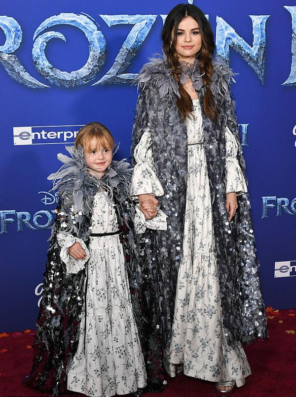 Selena Gomez và bé Gracie Teefey mặc đồ ton sur ton với váy hoa và áo choàng đính lông vũ, sequin.