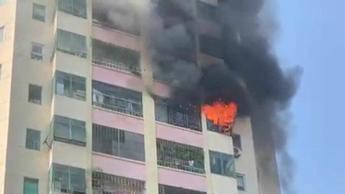 Lửa và khói đèn bốc lên từ căn hộ tầng 10, tòa A4, Làng quốc tế Thăng Long, quận Cầu Giấy, sáng 9/11. Ảnh: Nguyễn Ngoan.